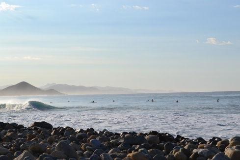 ocean dotted with surfers just after sunrise